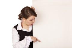 La donna sorpresa indica con la barretta sulla scheda in bianco Fotografia Stock Libera da Diritti