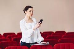 la donna sorride e scrive SMS sul telefono Fotografia Stock