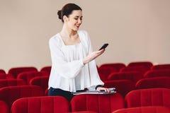 la donna sorride e scrive SMS sul telefono Immagine Stock