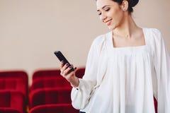 la donna sorride e scrive SMS sul telefono Immagini Stock