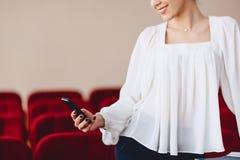 la donna sorride e scrive SMS sul telefono Immagini Stock Libere da Diritti