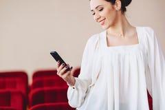 la donna sorride e scrive SMS sul telefono Fotografia Stock Libera da Diritti