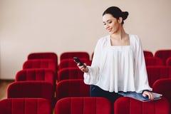 la donna sorride e scrive SMS sul telefono Fotografie Stock Libere da Diritti