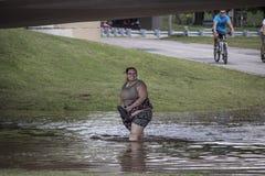 La donna sorride mentre guada attraverso acque di inondazione ripugnanti sotto il sottopassaggio dal fiume Arkansas durante l'ino fotografia stock