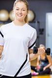 La donna sorridente in attrezzatura di allenamento tiene la testa di legno alla palestra di forma fisica Fotografie Stock