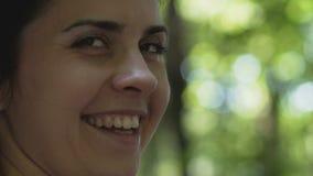 La donna sorridente cammina in foresta gira intorno felicemente, femmina gode della data del parco di vita archivi video