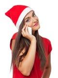 La donna sorridente in cappello dell'assistente di Santa parla dal telefono immagine stock