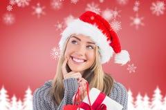 La donna sorridente in cappello di Santa che tiene un regalo insacca Fotografia Stock Libera da Diritti