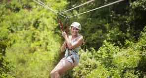 La donna sorridente che guida uno zip allinea in una foresta tropicale fertile fotografia stock