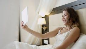 La donna sorridente che si trova a letto sta avendo una video chiacchierata sopra il suo pc della compressa archivi video