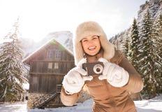 La donna sorridente che sta la montagna vicina alloggia e prendere le foto Fotografia Stock