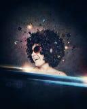 La donna sorridente con i capelli di afro ascolta musica con le cuffie Immagine Stock