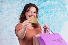 La donna sorridente con i sacchi di carta colourful di acquisto mostra il credito Ca Fotografia Stock