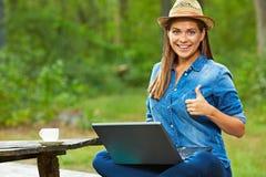 La donna sorridente con il computer portatile che si siede nel giardino mostra il pollice Immagini Stock