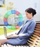 La donna sorridente con il computer portatile e lo zodiaco firma dentro la città fotografia stock