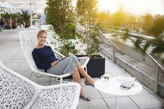 La donna sorridente con il cuscinetto di tocco sta godendo del suo tempo della ricreazione in caffè Fotografia Stock Libera da Diritti