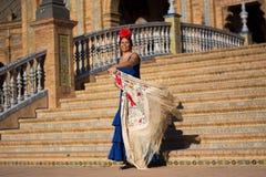 La donna sorridente con il vestito blu da flamenco in Plaza de Espana imita il movimento del ` s del toreador immagine stock libera da diritti
