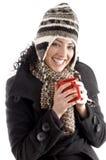 La donna sorridente con l'inverno ricopre la tazza di caffè della holding Fotografia Stock