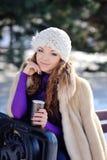 La donna sorridente con la tazza di caffè nell'inverno parcheggia Fotografie Stock