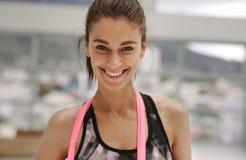La donna sorridente con la resistenza lega allo studio di forma fisica Fotografie Stock