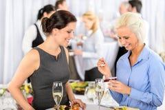 La donna sorridente del buffet di riunione d'affari mangia il dessert Immagine Stock