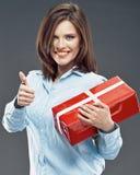 La donna sorridente di affari tiene il pollice rosso di manifestazione del contenitore di regalo su Fotografie Stock Libere da Diritti
