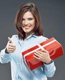 La donna sorridente di affari tiene il pollice rosso di manifestazione del contenitore di regalo su Fotografia Stock Libera da Diritti