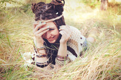 La donna sorridente di giovane hippy con la fascia sulla sua testa ha una menzogne di divertimento all'aperto in parco soleggiato Fotografie Stock Libere da Diritti