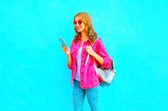 La donna sorridente di modo sta utilizzando lo smartphone nel rivestimento rosa del denim Fotografie Stock Libere da Diritti