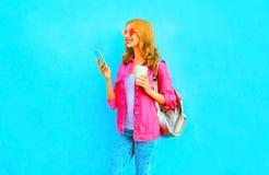 La donna sorridente di modo sta utilizzando lo smartphone nel rivestimento rosa del denim tiene la tazza di caffè Fotografie Stock