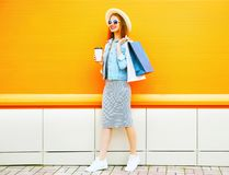 La donna sorridente di modo tiene una tazza di caffè, sacchetti della spesa che portano un cappello di paglia Immagine Stock