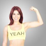 La donna sorridente di sport ostenta i suoi muscoli su fondo grigio Sport e forma fisica Immagine Stock Libera da Diritti
