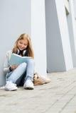 La donna sorridente di studio dei giovani ha letto il libro esterno Fotografie Stock