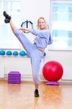 La donna sorridente fa l'allungamento dell'esercitazione Immagine Stock Libera da Diritti