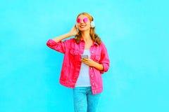 La donna sorridente felice ascolta musica in cuffie senza fili con lo smartphone in rivestimento rosa del denim Fotografia Stock Libera da Diritti