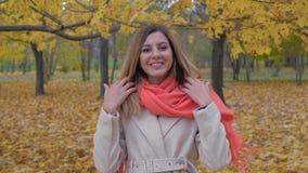 La donna sorridente felice in Autumn Park With Yellow Foliage raddrizza i capelli video d archivio