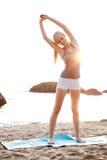 La donna sorridente felice che fa l'allungamento si esercita durante l'yoga Fotografia Stock Libera da Diritti