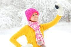 La donna sorridente felice fa l'autoritratto sullo smartphone nell'inverno Fotografia Stock