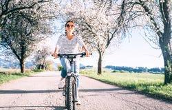 La donna sorridente felice guida una bicicletta sulla strada campestre nell'ambito del bl fotografia stock