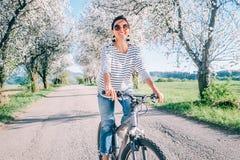 La donna sorridente felice guida una bicicletta sulla strada campestre sotto gli alberi del fiore La primavera è immagine venente fotografia stock