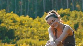 La donna sorridente felice si siede su un'erba verde in un campo scenico su un fondo del tramonto archivi video