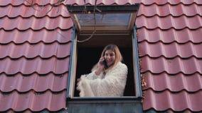La donna sorridente fortunata apre una finestra nella casa e la conversazione sul telefono video d archivio