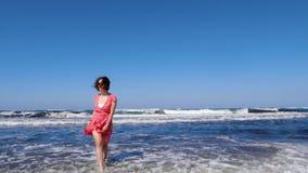 La donna sorridente giovane invita un uomo a seguirla che cammina verso il mare Forti onde che colpiscono la spiaggia Vestito ed  video d archivio