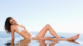 La donna sorridente gode di di prendere il sole sul bordo dello stagno Immagini Stock Libere da Diritti