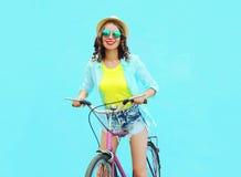 La donna sorridente graziosa guida una bicicletta sopra il blu variopinto Fotografie Stock