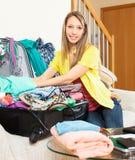 La donna sorridente imballa la valigia Fotografia Stock