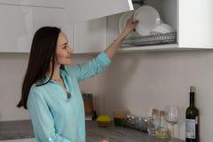 La donna sorridente mette i piatti puliti sullo scaffale dell'essiccatore all'interno di una cucina bianca, soluzioni moderne per immagine stock