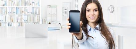 La donna sorridente mostra lo smartphone isolato sul busin interno dell'ufficio fotografie stock libere da diritti