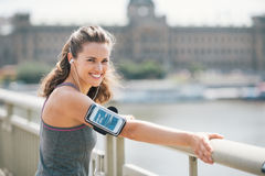 La donna sorridente nell'allenamento innesta ascoltare la musica dal fiume della città Fotografie Stock Libere da Diritti