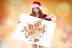 La donna sorridente in Santa costume la tenuta del cartello con il saluto di natale Fotografia Stock Libera da Diritti